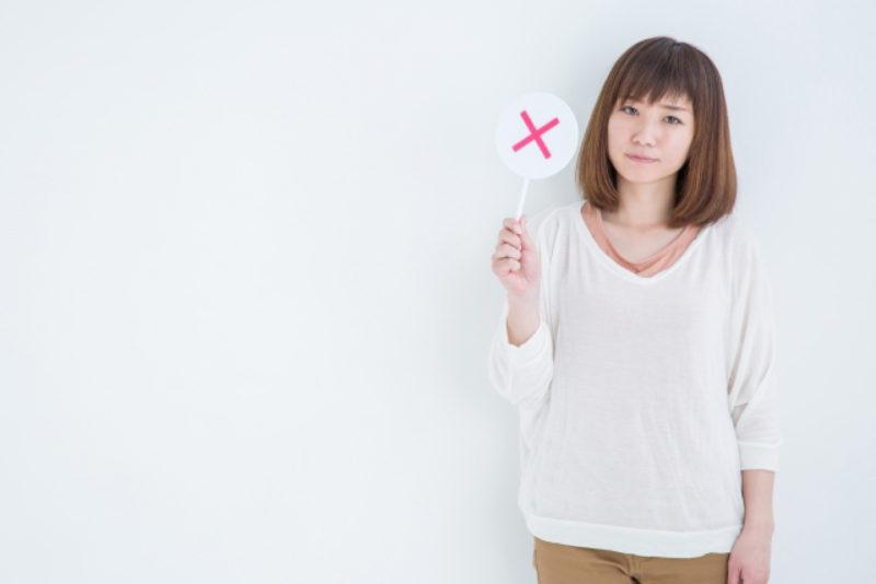 女性 バツ印の札